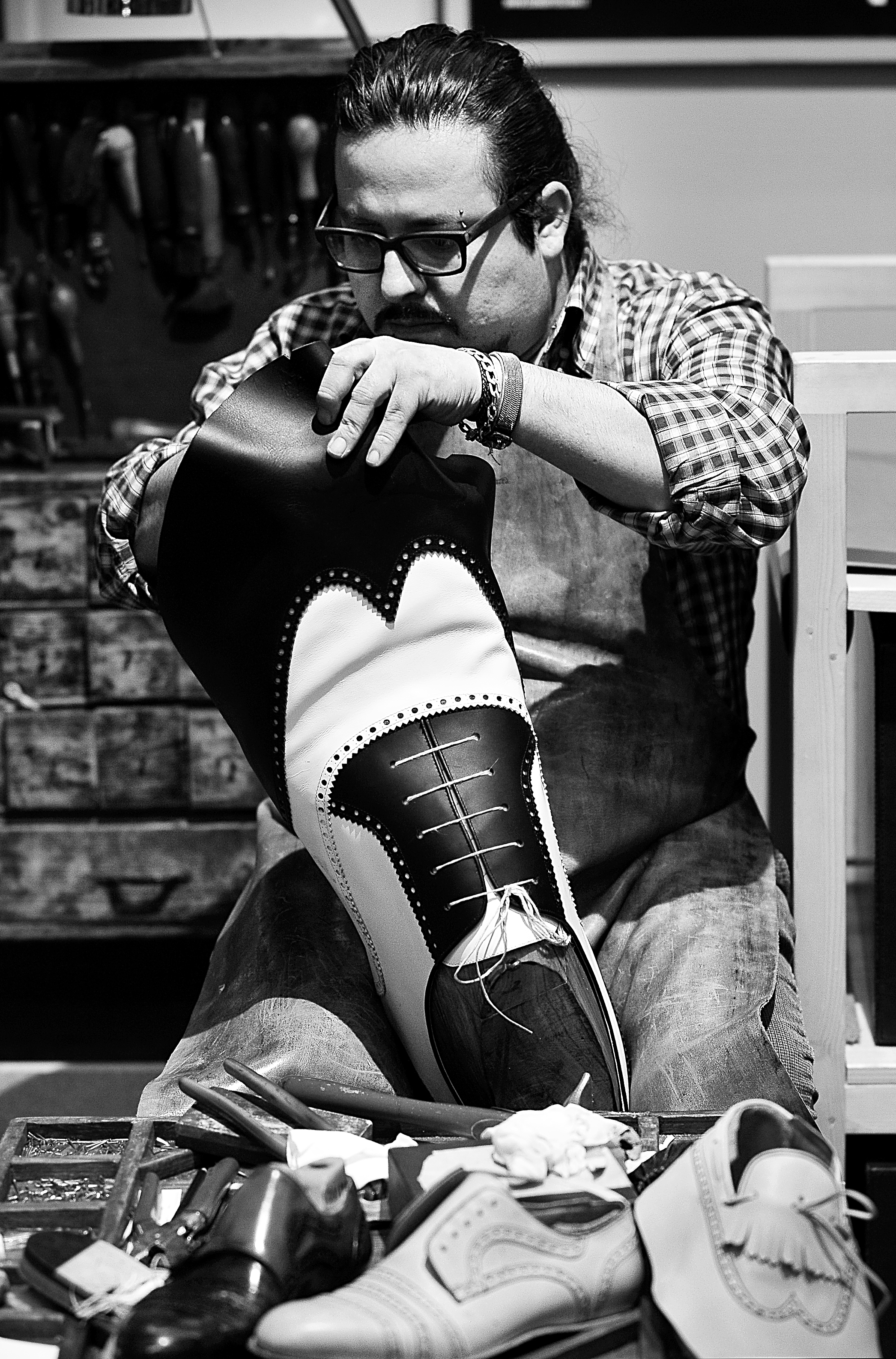 Peruvian-born, Italian educated artisan Giancarlo Zeggara, 39, crafts bespoke shoes for consortium Cuoio di Toscana at Pitti Uomo<br /> Photo by Silio Danti